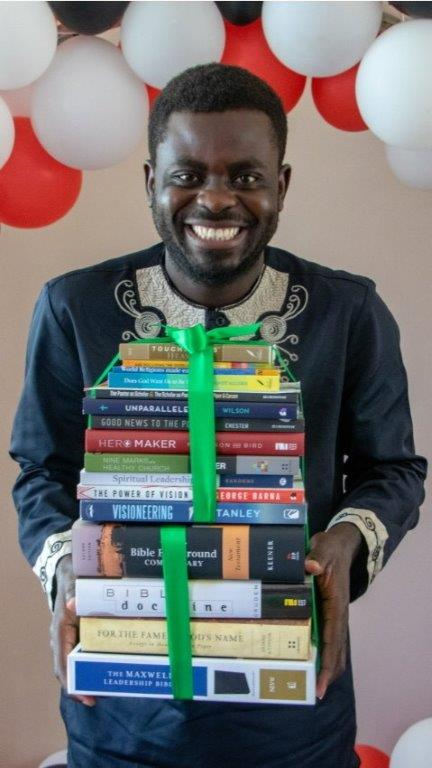 Bible college graduate in Uganda receiving personal library of books