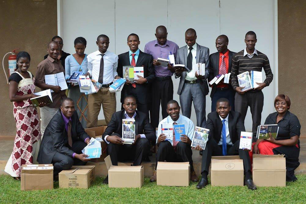 Group of Bible college students in Zambia holding book sets